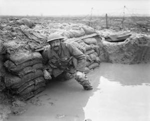 A sergeant of the Lancashire Fusiliers in a flooded dugout opposite Messines near Ploegsteert Wood, January 1917. © IWM (Q 4665)
