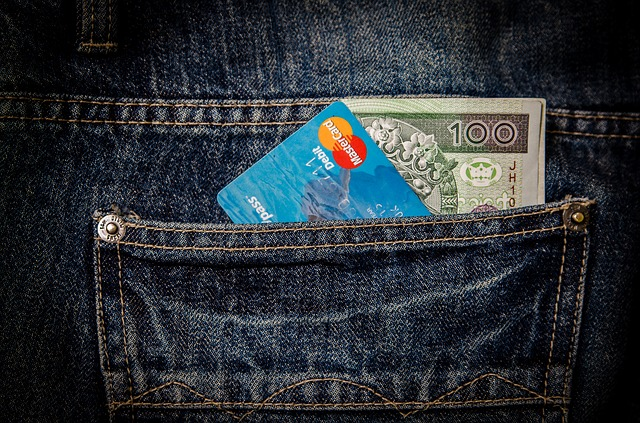 A jeans pocket with a credit card and cash in it.